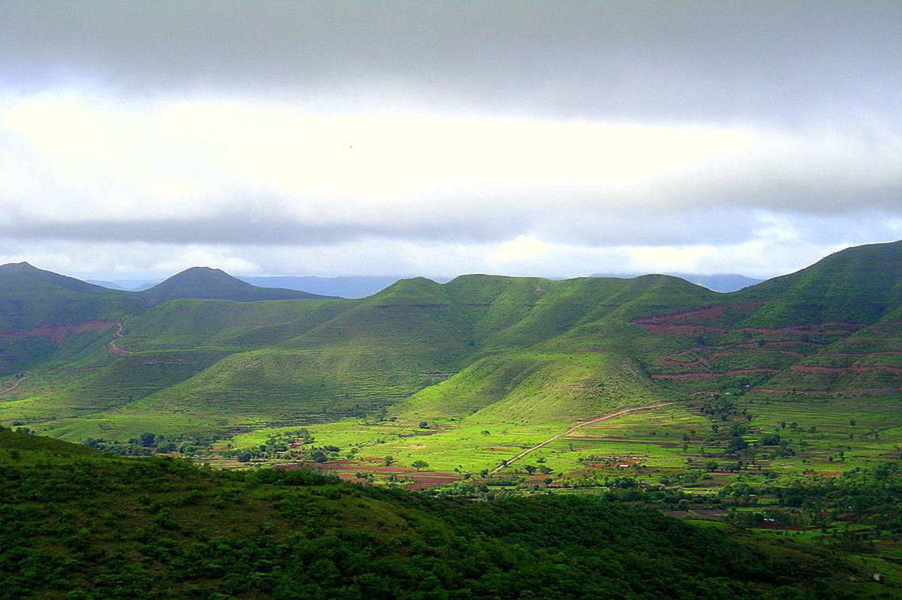 With grey cloud in sky in a monsoon season, the sun shines on the green mountains of western ghats