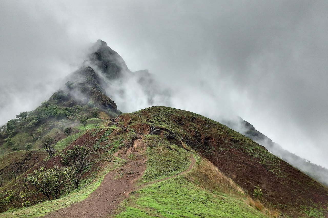A trail passing through the mountain peak to the less visible mountain peak covered with grey fog on a monsoon season