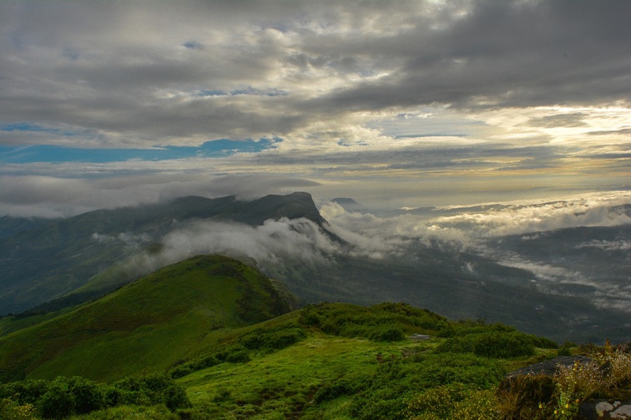 green lavish mountains of western ghats with cloudy sky above and fog below the mountain peak