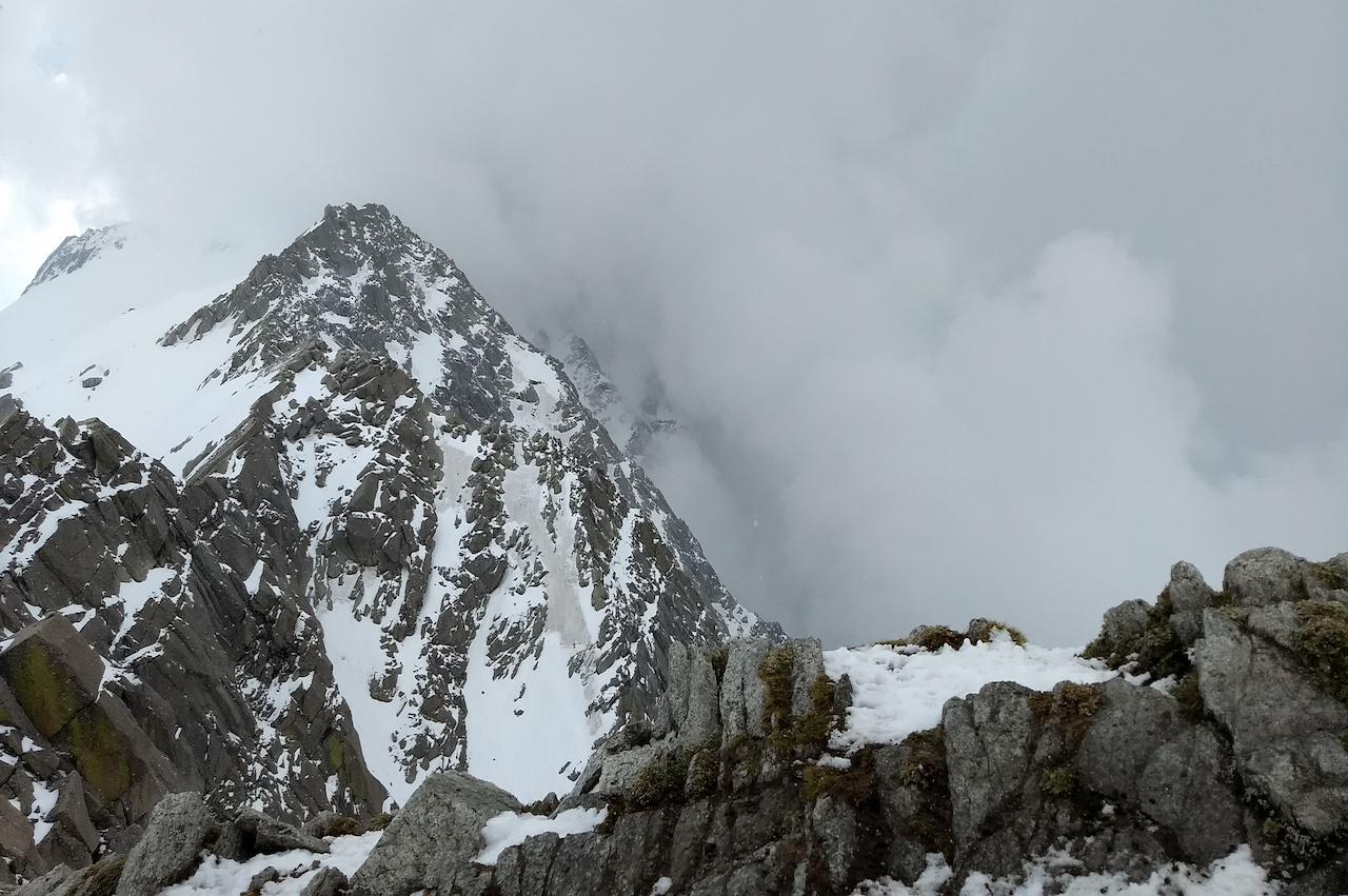 Ridge of a high altitude mountain with snow trails with big rock blocks surrounded by the grey fog like path to heaven