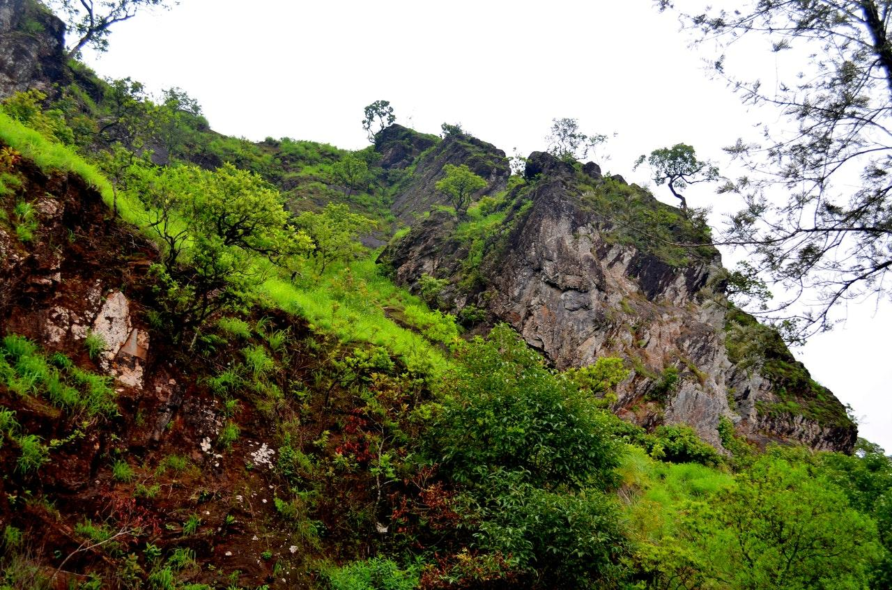 Huge block of rock in a mountain slope covered with green grass and trees on a sky full of grey cloud