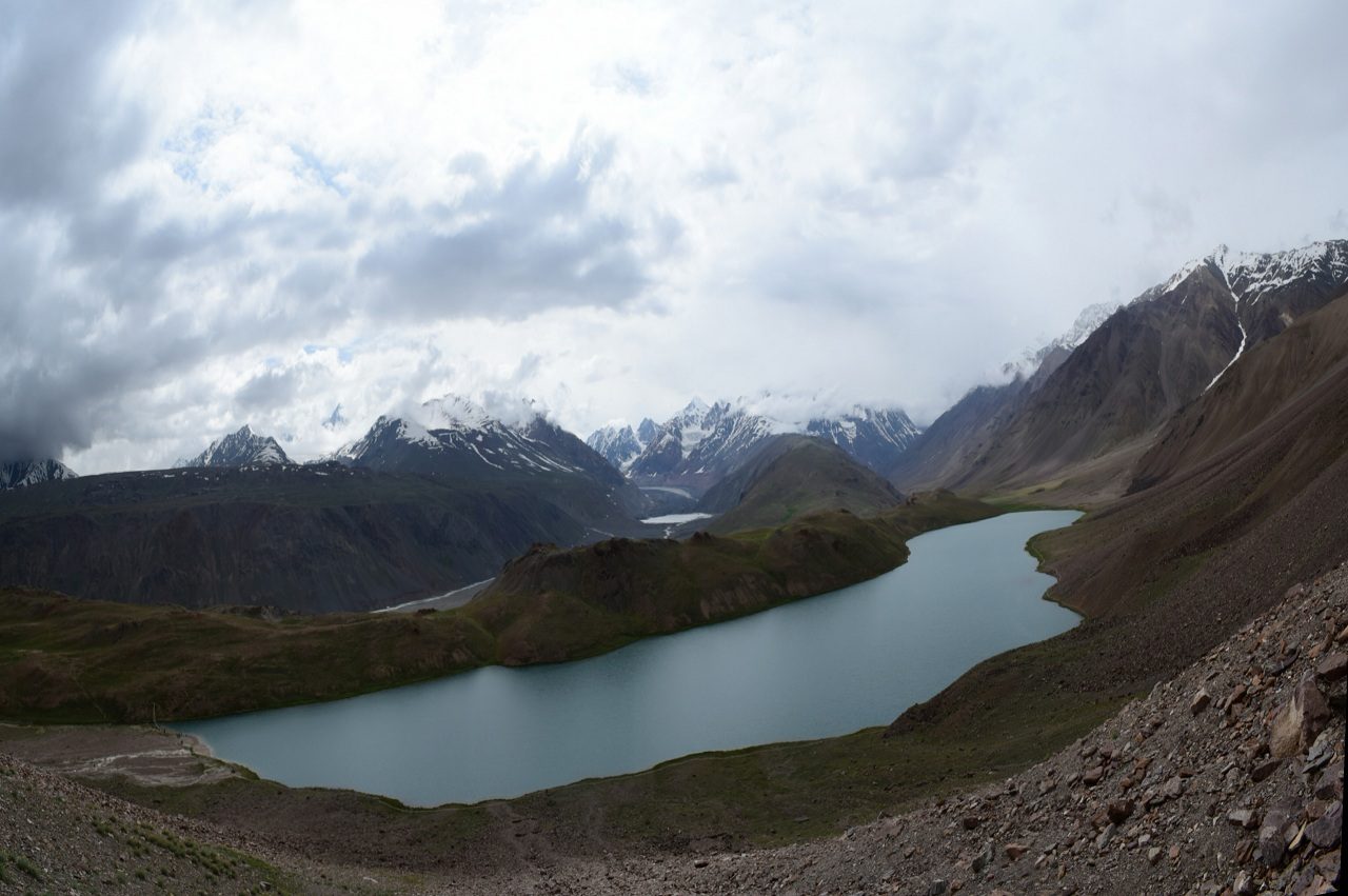 crescent shaped chandratal lake with snow capped mountains in distant