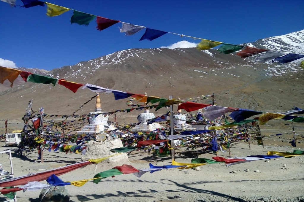 colourful cloth tied around the rope surrounding group of small temples at kunzum la