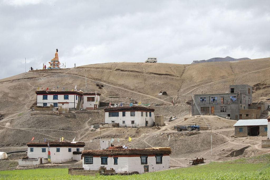 lanza village with couple of houses and buddha statue lying at the top of hill