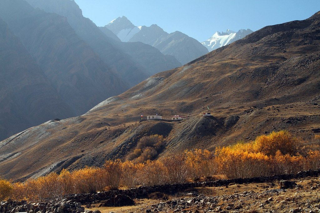 couple of houses in losar village with visible snow capped mountains peak on other side of hill