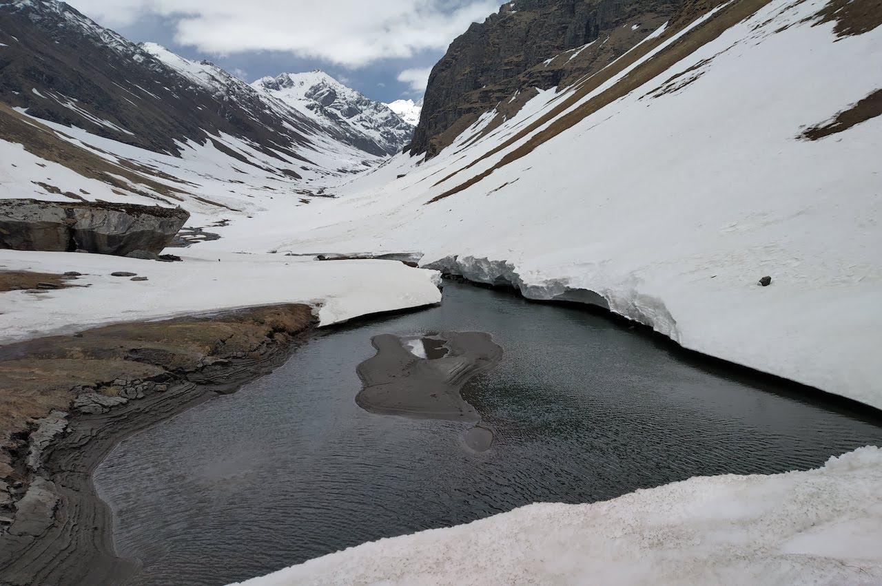 Maninda lake in the middle of valley with snow covered mountain dripping water in it