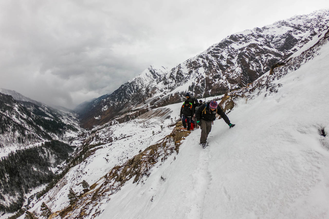 Trek leader making way for fellow trekkers in the Har ki dun valley through snow covered mountian with cloudy sky above
