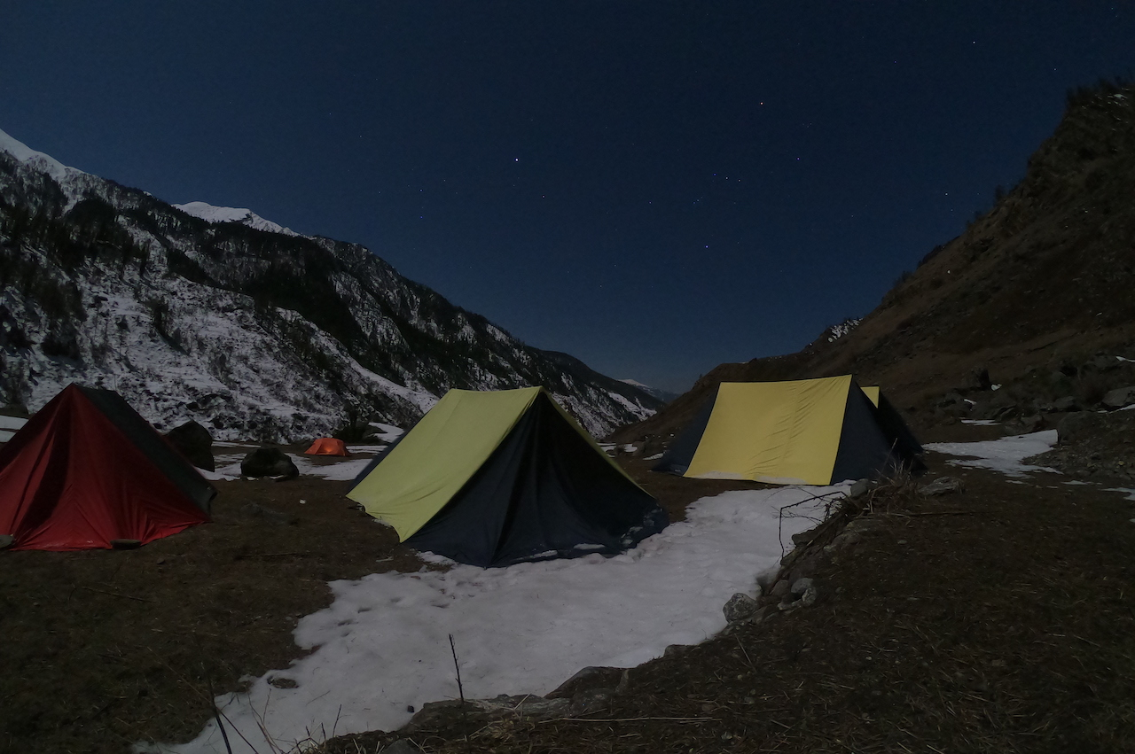 Campsite at the foot of snow covered mountain under the sky full of stars