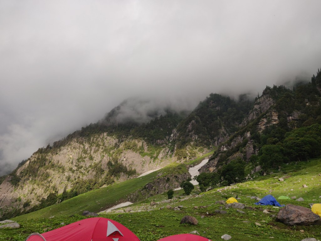 tents pitched on a plain ground in mountain slope with fog covering top of mountain peak