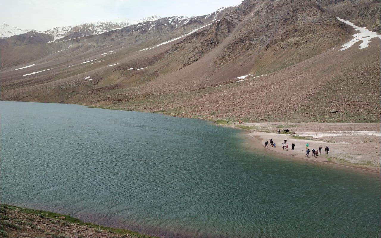 people standing near the chandratal lake