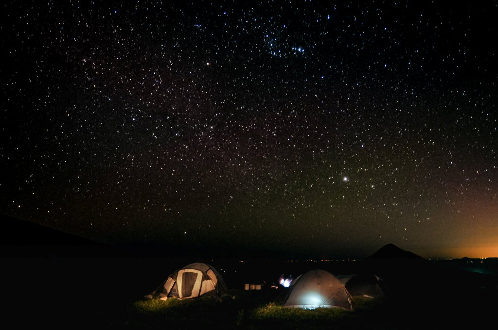 couple of tent pitched on ground at the night with sky full of stars