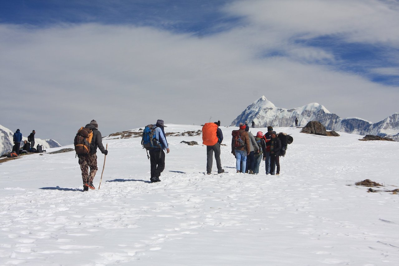 trekkers carying racksack walking toward the brahmatal summit