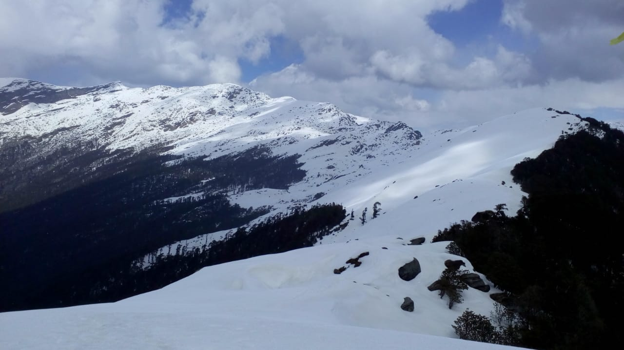 ridge of snow covered mountain at brahmatal trek