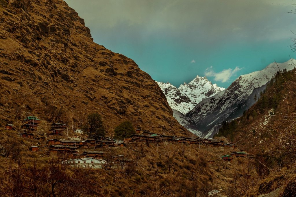 Gangad village lying on the slope of mountain with visible snow capped himalayan mountain on back