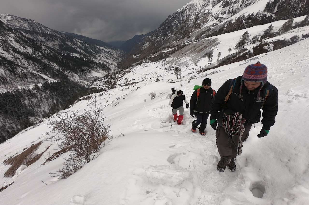 trek leader leading the way through snow covered slope of kalkathiyar dhar