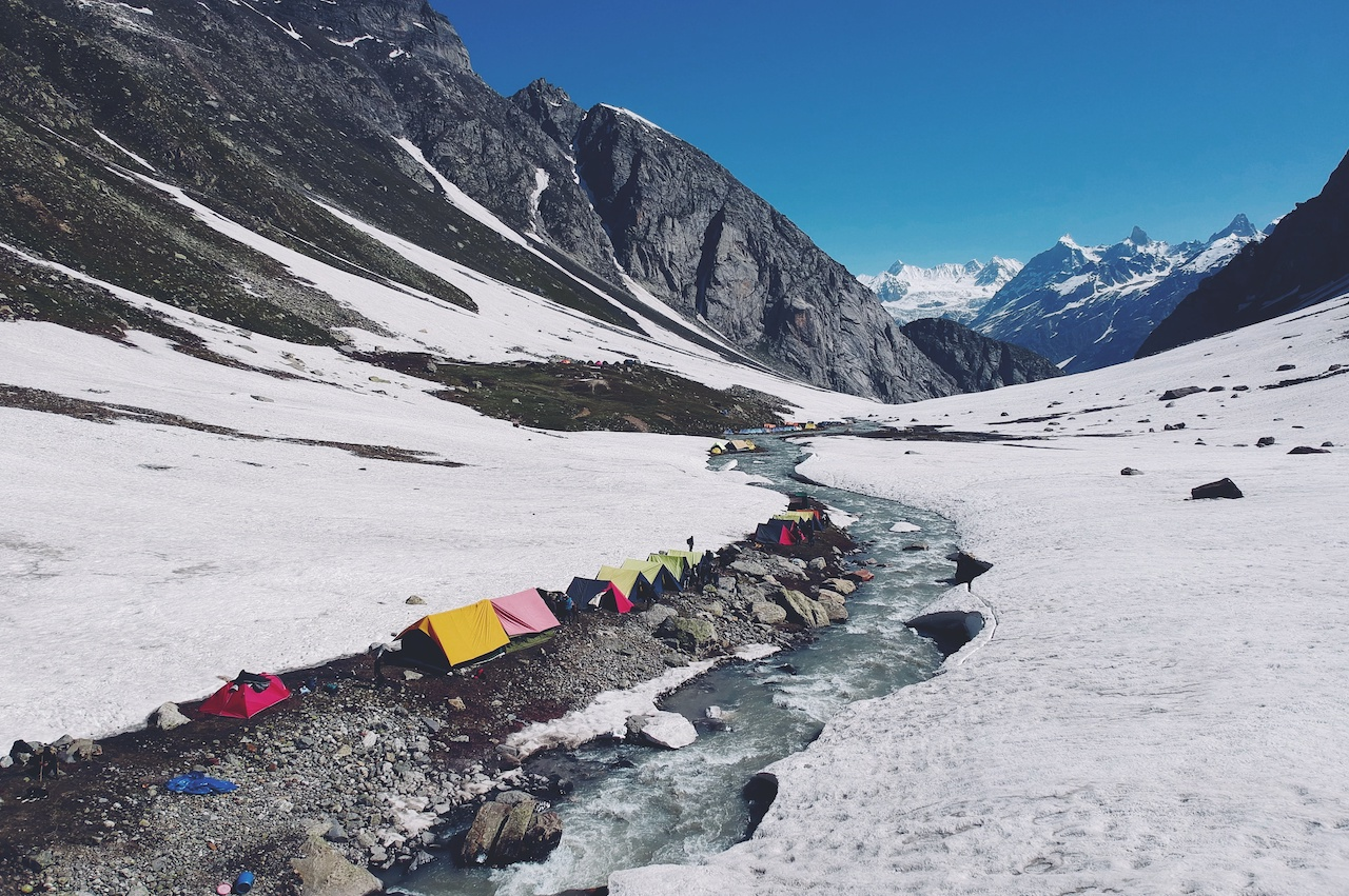 Colorful tents beside the flowing stream of water surrounded by snow covered ground at Balu ka ghera campsite with distant view of Indrasan massif