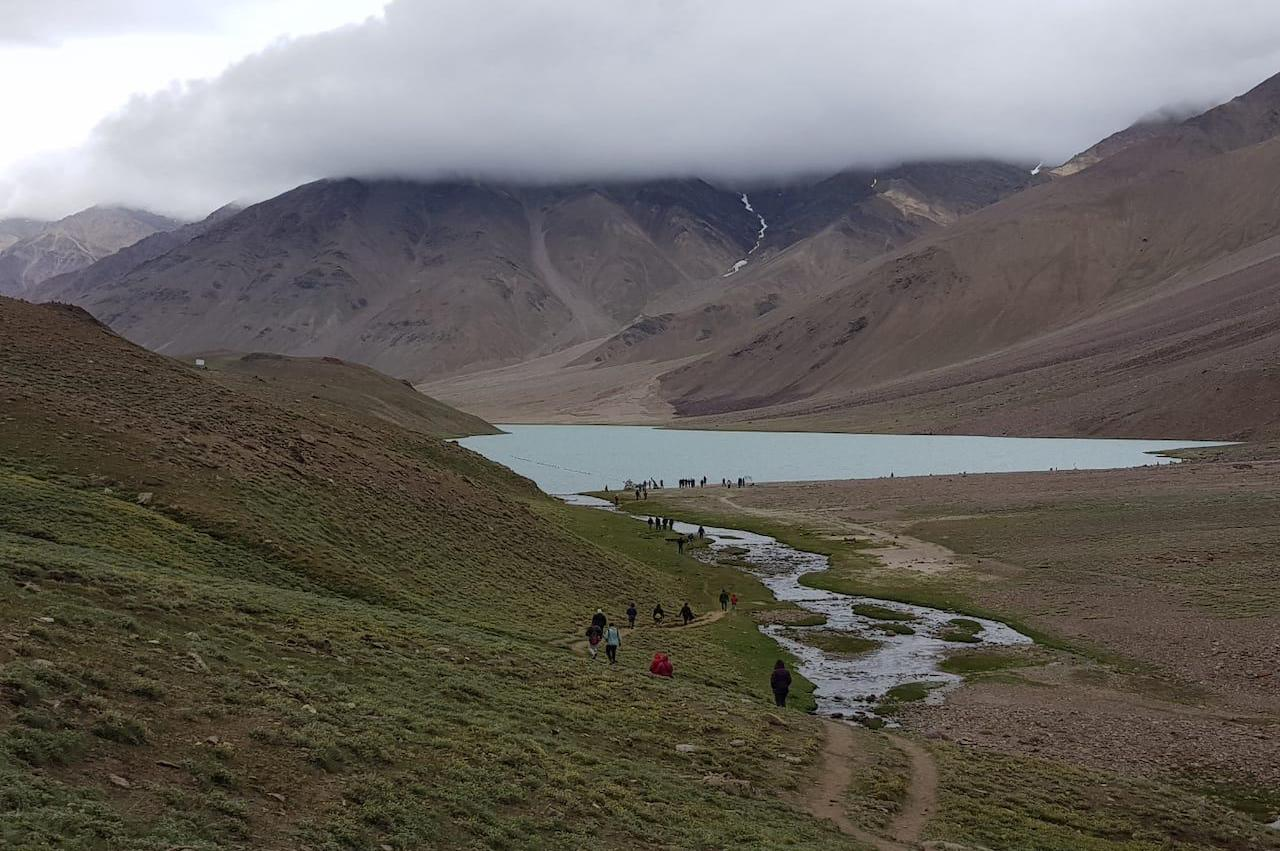 People walking toward the Chandratal lake through the single trail with Fog over the lake hiding the peak of mountain in front