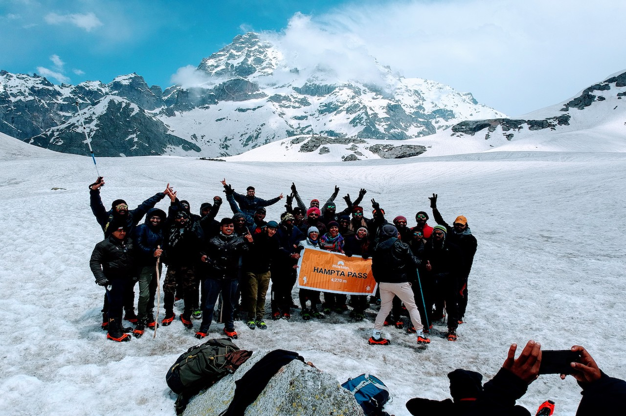 Group of trekkers holding the banner of moxtain standing at the snow covered hampta pass valley