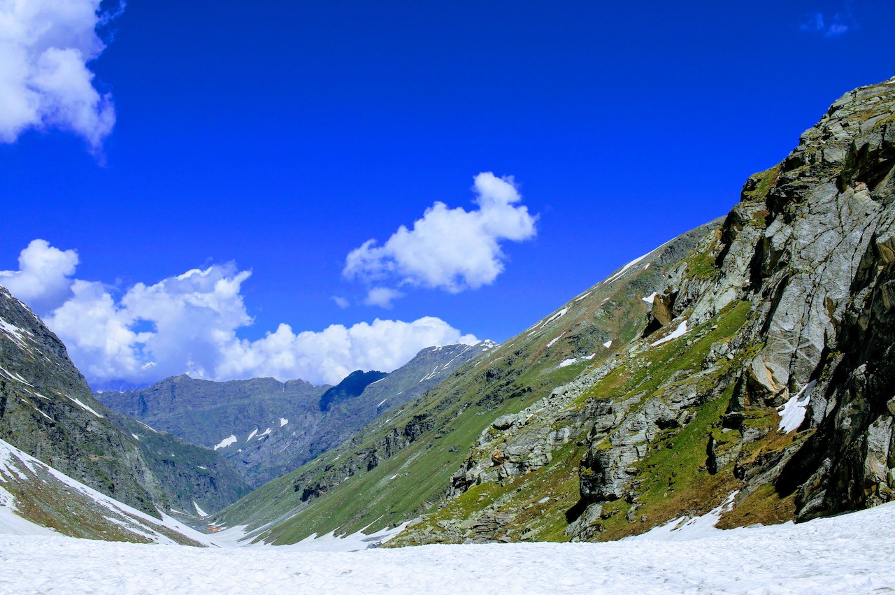 A valley surrounded by huge mountain covered with green grass and and big block of stone enroute hampta pass with couple of clouds over head on blue colour sky