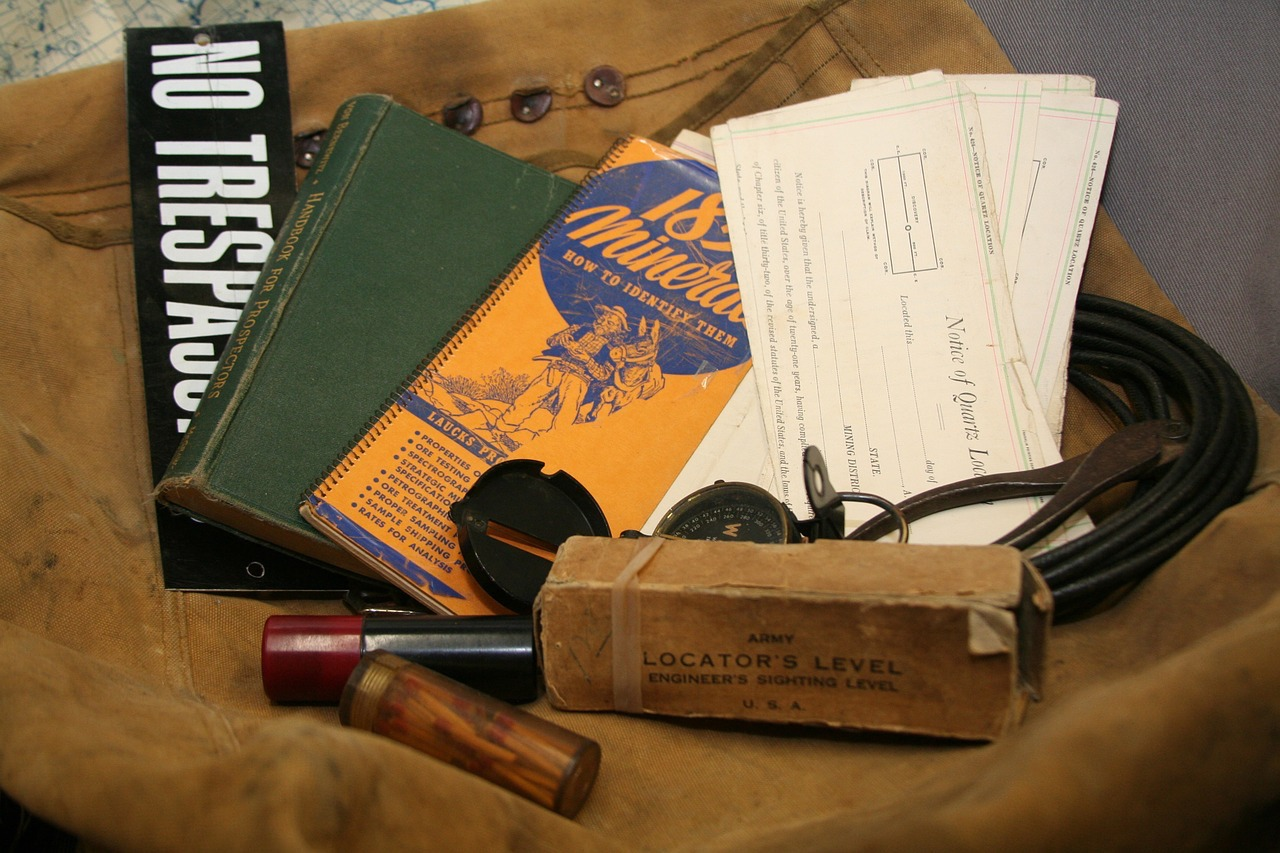 A ice axe, rope, couple of books, a compass placed over a brown bag