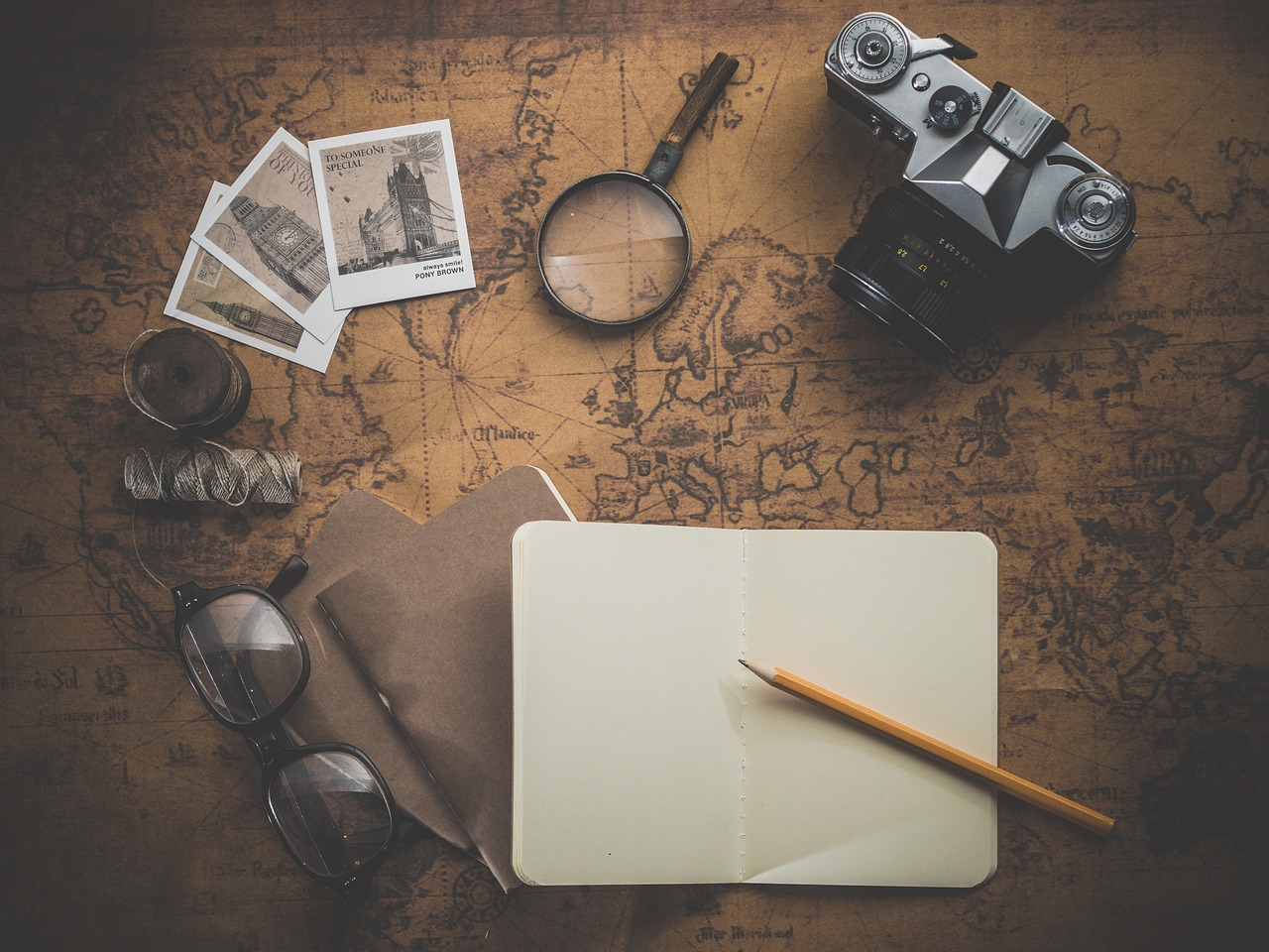 A notebook, pen, goggles, camera, magnifies, and a couple of stamp lying over world map