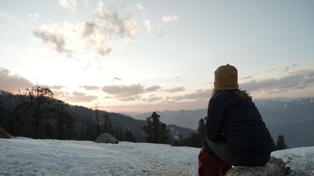 trekker watching the sunset in himalayas