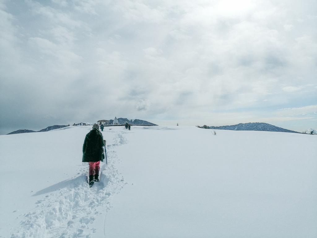 trekker walking on snow covered trail
