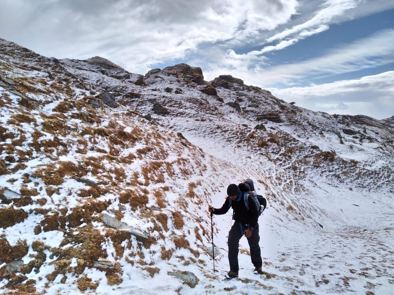 trekker holding trekking stick walking over snow covered ground