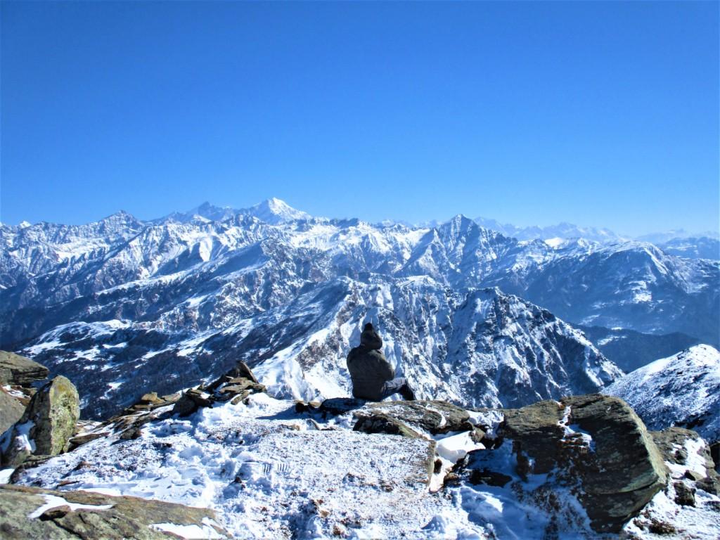 Trekker sitting at the edge at kedarkantha summit