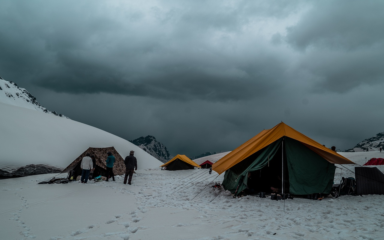 people standing at campsite with grey cloud covering the sky