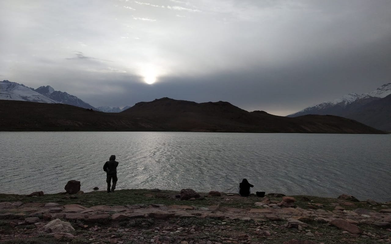people standing near chandratal lake with sun shining through the cloud