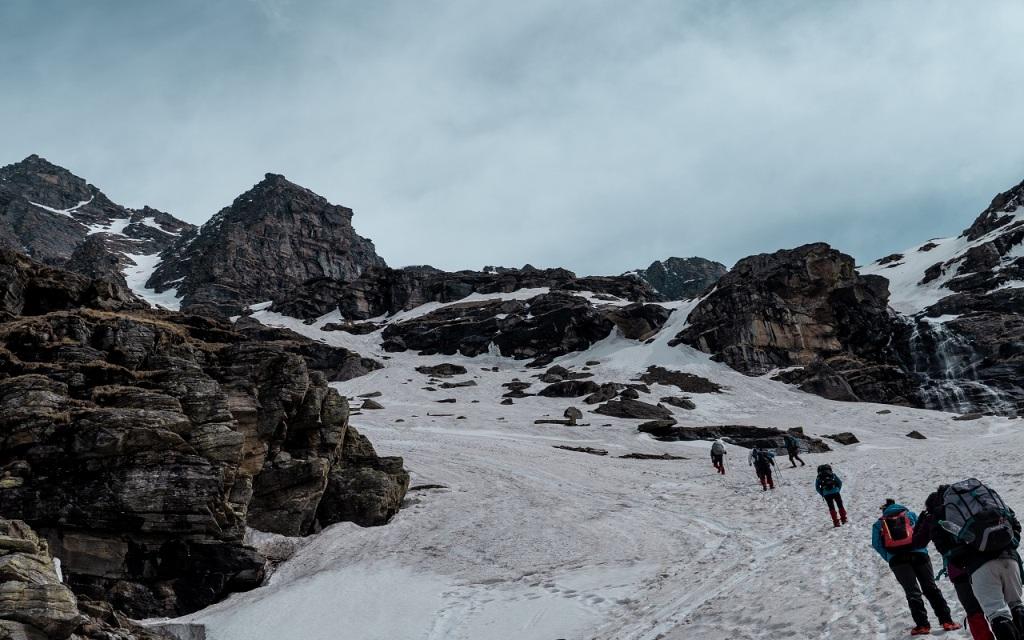 trekkers heading toward the snow capped rupin pass