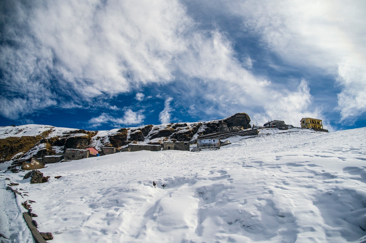 snow covering the ground in Tungnath with houses and tungnath temple on the way to chandrashila with couds shattering in the sky