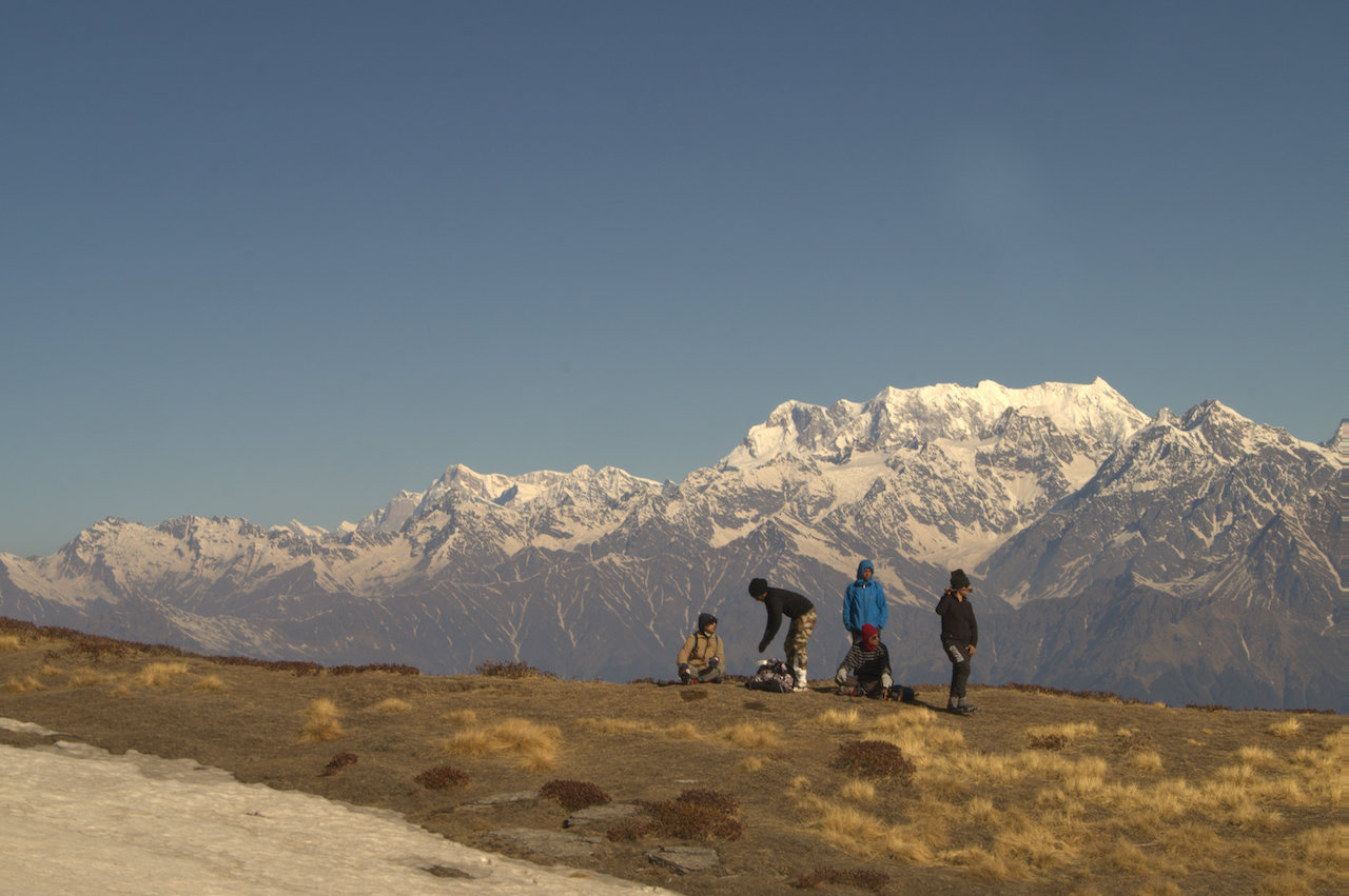 group of 5 people taking rest on the way to kuari pass looking at the snow covered chaukambha massif under the clear blue sky