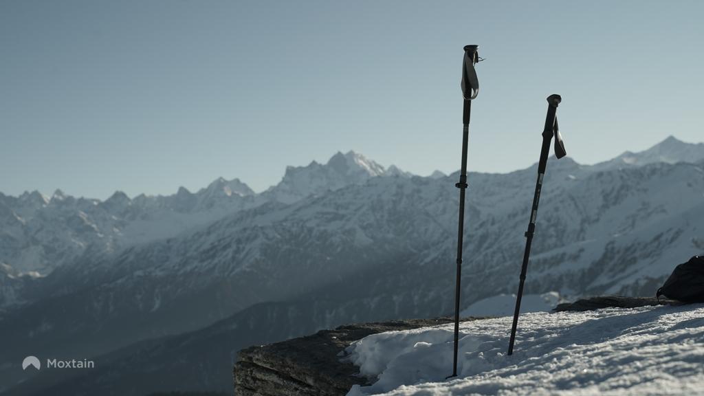 trekkign poles pitched on snow