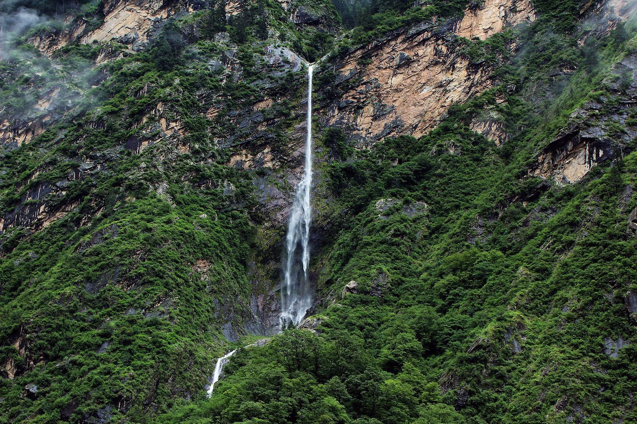 waterfall dropping from high mountain slope covered with green tree