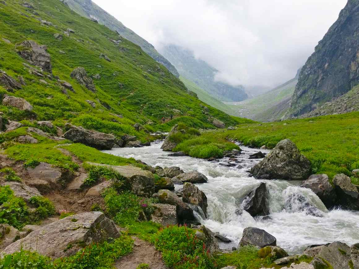 river flowing along the valley of lavish green mountains in hampta pass valley