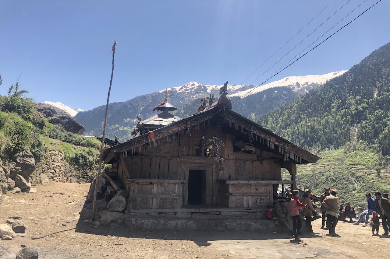 People standing beside wooden temple enroute Har ki Dun
