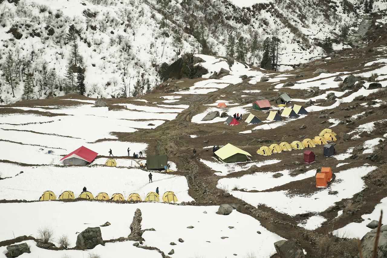 Multi colour tent pitched at campsite surrounded by beautiful mountain covered with snow