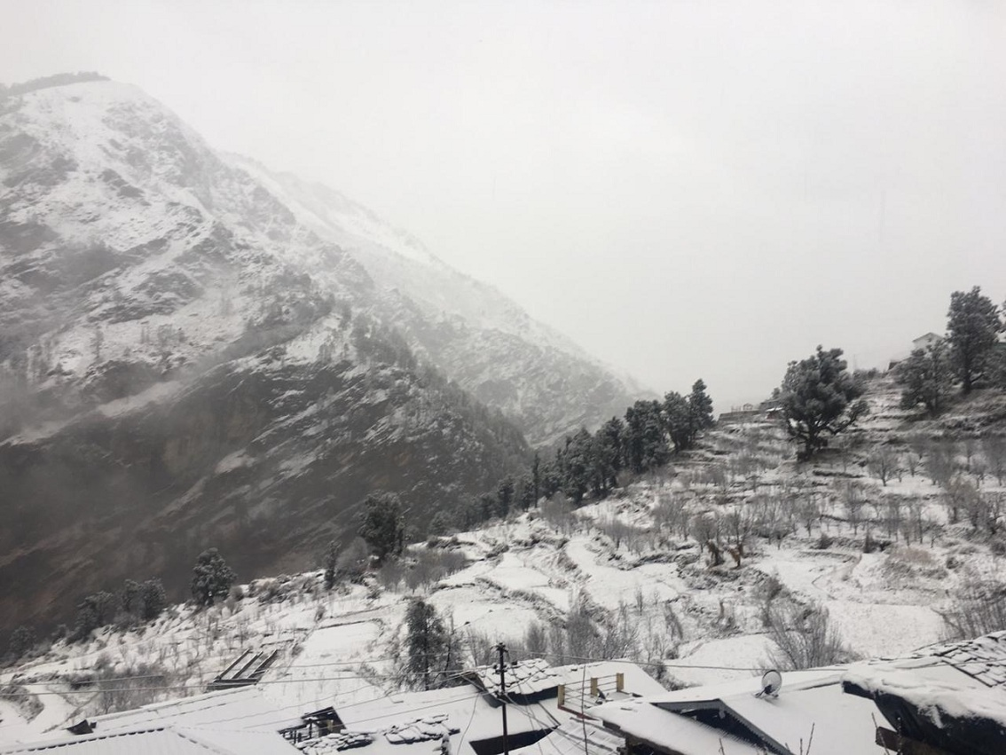 With fog covereing the back, the snow covered sankri village in the slope of himlayan mountain looks like a painting