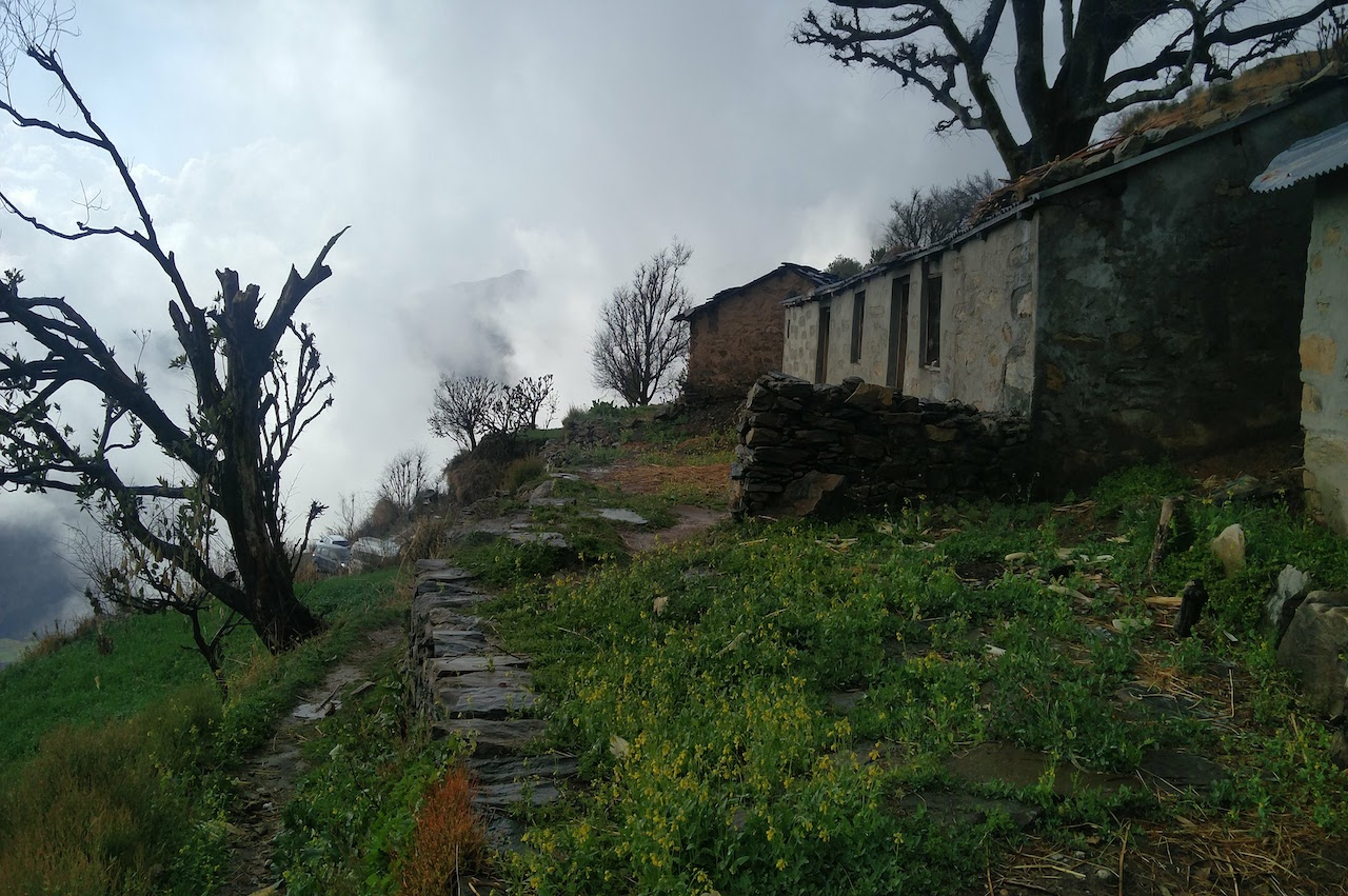 trail to nag tibba base camp passes through the village with old stone homes with greenary all around and blue sky with fog spread