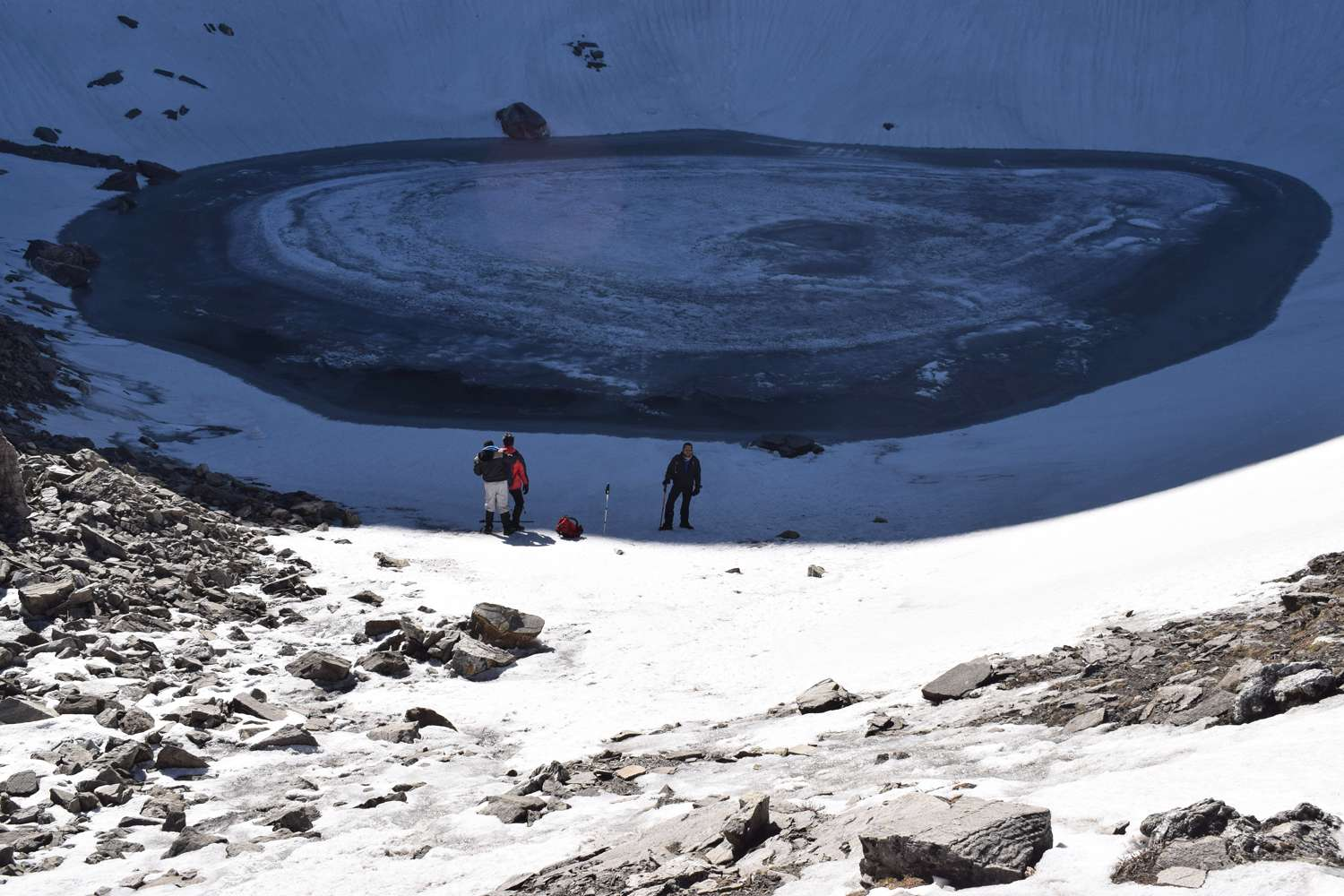 3 people standing over frozen roopkund lake