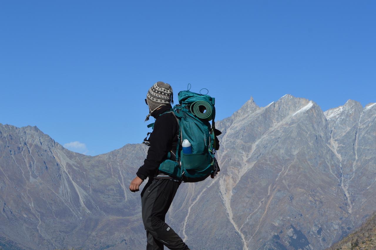 Man wearing black jacket carrying blue backpack going downhill in garhwal himalaya region